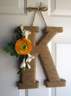 Layered cardboard letter wrapped in twine. Floral accent can be changed for different seasons.