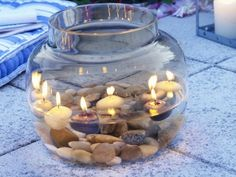 big jar of candles floating in water and river rocks