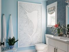 HGTV.com shares stunning pictures of the terrace bathroom. Brilliant blue penny tile walls bring a coastal touch into the guest bathroom, while a sleek white vanity and eye-catching artwork add interest.