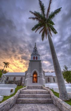 Passed by this place many times. The burial crypts are owned by families who bury their loved ones deep. Trinity Church in Bermuda at sunrise with golden glow from inside and royal palm and steps in front. Bermuda Vacations, Bermuda Travel, Cruise Vacation, Beautiful Places To Travel, Chapelle, Place Of Worship, Beautiful Islands, Caribbean, Places To Visit