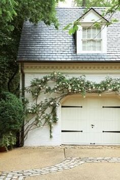 Add elegance to the front of any home with a wooden garage door, old accessories, and climbing rose bushes.