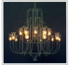 "7046  TWENTY LIGHT TWO TIER IRON CHANDELIER FINISH SHOWN: CUSTOM SHADE: SHOWN WITH HURRICANE GLASS, AVAILABLE WITH 3X8X5 SHADES  AND WAX CANDLES MAXIMUM WATTAGE: 1200 CANDELABRA BASE SOCKETS HT 60"" W 60"" APPROX. WT. 75 LBS. REQUIRES REINFORCED J-BOX"