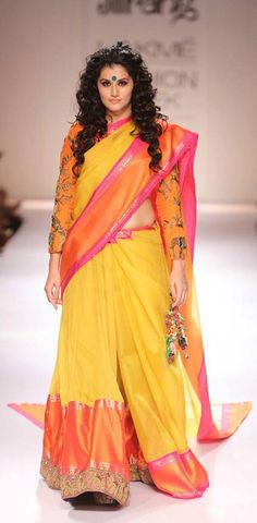 Actress Taapsee Pannu walked the ramp in a yellow ghagara with a gold-and orange border with full sleeved orange blouse and dupatta draped as a sari pallu.