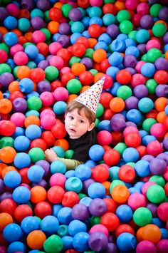 photo of birthday kid in polka dot hat in a giant pit of balls