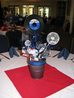Most centerpieces lay the record flat in the center.this is an alternative way to incorporate a record to bring height to the centerpiece. Not sure how disco balls are, but know I've seen them around cheaply. Decade Party, 70s Party, Disco Party, Motown Party, Grease Party, Disco Theme, Rock Star Party, 70th Birthday Parties, Music Party