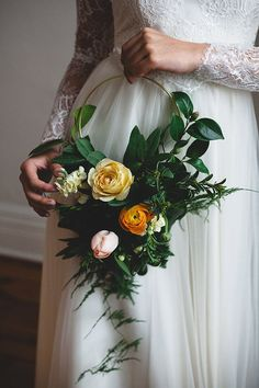 Hoop bouquets are an emerging trend in wedding floral design. This one features a cluster of garden roses, tulips, and ranunculi framed by wispy ferns and lush foliage in the deepest of greens. | Photo by Frances Beatty