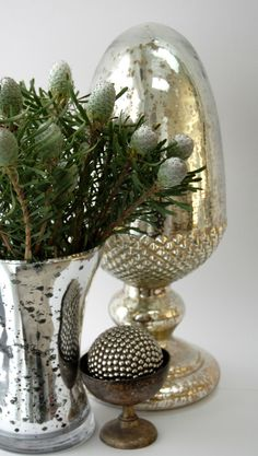 Leucadendron Alpinii's beautiful silvery heads, a mercury glass acorn, and studded ball in a tarnished silver dish
