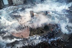 People run away as Turkish riot policemen fire tear gas on Taksim square on June 11, 2013. Turkish police fired massive volumes of tear gas during Gezi Protests.