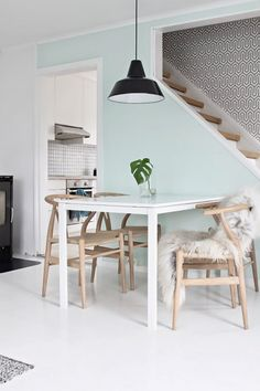 Industrial inspired dining space with Hans J. Wegner wishbone chairs, a pendant lamp, and a mint green contrast wall