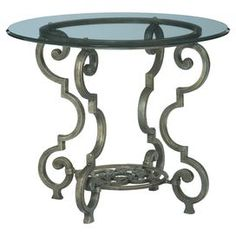 """Showcase framed photos and decor on this elegant accent table, featuring a glass top and scrolled metal base.   Product: Accent tableConstruction Material: Metal and glassColor: Silver and clearDimensions: 25"""" H x 30"""" Diameter"""