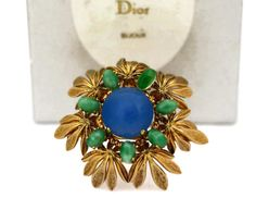 Features: - 100% Authentic CHRISTIAN DIOR. - 3 dimensional flower brooch. - Blue and green glass cabochons embellishment. - Gold tone hardware. - Signed CHRISTIAN DIOR 1965 Made in Germany. - Comes with Christian Dior box and silk protective cover. - One green cabochon has been replaced. - Very good vintage condition.  Measurements: Height: 1 6/8 inches Width: 1 5/8 inches Depth: 7/8 inch  **This brooch will be shipped via Priority Shipping with tracking number.  Please convo m...