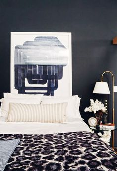 Deep blue and neutral bedroom with cool artwork