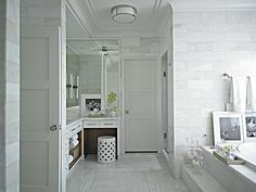 Floor-to-ceiling Carrera marble walls lend a bright aspect to this sophisticated bathroom.