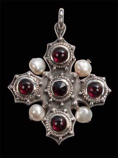 Ornate 15th century reliquary cross in silver with granuled decoration. Set with one 6mm rose cut Garnet in the centre and four cabachon cut garnets on the arms of the cross, four baroque freshwater pearls are also threaded between the arms.  This is a copy of a gilded silver 15thc German cross from the V and A collection, the garnets may represent the blood of Christ and the Pearls are symbolic of purity.