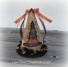 Pinner said:  One of my favorite primitive Halloween designs has been cross stitched and finished into a delightful tabletop decoration. The cross stitch