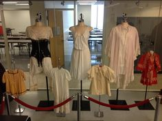 Victorian undergarments: including corset, a combination suit and nightgown with pink combing cape.  The children's wear includes christening gown, coat and a red dress with matching cape.