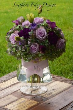 Antique purple hydrangea with lavender Ocean Song roses, purple Moonstruck carnations and purple Lisianthus ~ all make up this beautiful floral centerpiece by Southern Edge Design
