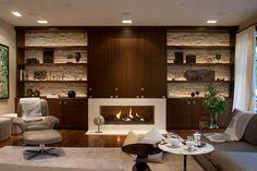 Combinacion de piedra y gabinetes y repisas modernas + chimenea.  La TV puede estar escondida arriba de la chimenea.