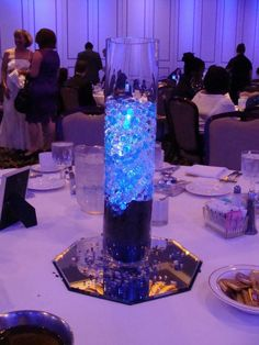 We used blue and white gel beads for this centerpiece for a fundraiser.  They matched deliciously with the uplighting on the wall.  Wish I had a better room shot.