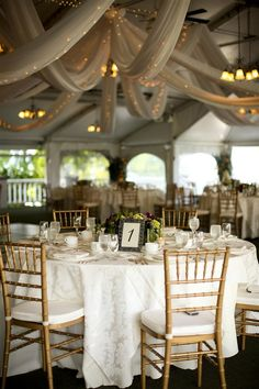 Beautiful tented reception with gauzy, tulle swags and tiny lights; gorgeous!