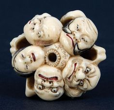 An ivory netsuke. 19th century Manju, signed Hakuosai. A very well carved and rare Manju netsuke with twelve juxtaposed Noh masks. Sumi (ink) hairwork and red lips. Hakuosai. Active 1830 - 43 was the foremost carver of this type of work. Ex Gilbertson collection. Diameter 4.3 cm