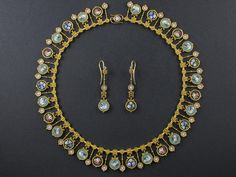 Parure composta da collana e paio di orecchini in oro giallo e micromosaici raffiguranti fiori e colombe. Gioiello di provenienza...