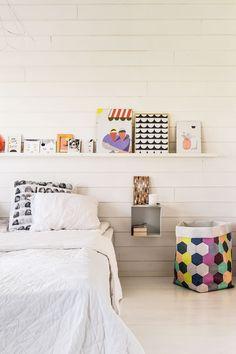 Samin ja Rillan makuuhuoneen seinäpaneeli hankittiin K-raudasta ja maalattiin valkoiseksi. Yöpöytinä toimivat seinähyllyt ovat Lehtorinteen, tauluhylly on Ikeasta. Värikäs pussi on Varpusen. Rilla on tutustunut bloginsa kautta Kanelimaan Hanna-Riikka Heikkilään, jonka töistä hän pitää kovasti. Yöpöydällä on Hanna-Riikalta saatu pisarateos. Päiväpeitto löytyi kirpputorilta.