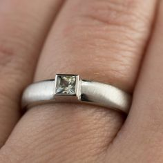 Modern simple engagement or wedding ring with a princess cut creamy yellow/white sapphire set in a low profile bezel setting on a rounded ring shank. The ring was carved out of wax, cast in silver/ pa