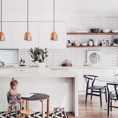 Thursday morning kitchen inspo! It's no secret I love a great feature tiled splash back and open shelves in a kitchen. And how amazing does this herringbone pattern look? Using a darker grout makes the pattern appear prominent, and the copper pendants are just perfect here. This cool kitchen belongs to fashion stylist @kristinrawson and was featured in @adoremagazine earlier this year. Styling by @peepmystyle  and  by @hannahblackmore ☀️
