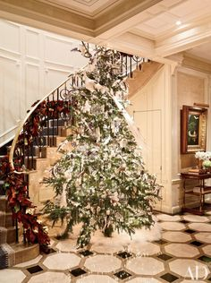 In the entrance gallery of a Manhattan family's duplex apartment stands a Mongolian-sheepskin–skirted Christmas tree, part of the decor created by event-planning firm Van Wyck & Van Wyck; a gilded magnolia garland traces the staircase's balustrade. Elegant Christmas, Very Merry Christmas, Beautiful Christmas, Christmas Holidays, Christmas Decorations, Christmas Trees, Christmas Christmas, Christmas Lights, Christmas Displays