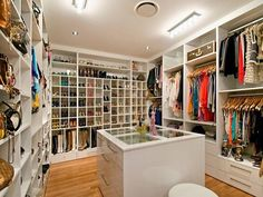closets - walk in closet, walk in closet design, closet island, glass top island, see through island, floor to ceiling shoe shelves, floor to ceiling boot shelves, shelves for shoes, shelves for boots, designer bags,
