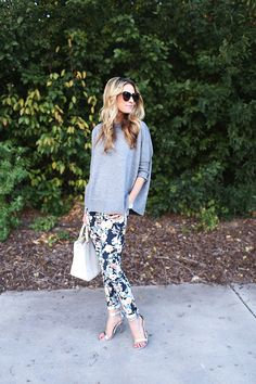 Emily Jackson is wearing a grey top from J. Crew, floral pants from 7FAM, silver sandals from Lulu's, white bag from Tony Burch and sunglass...