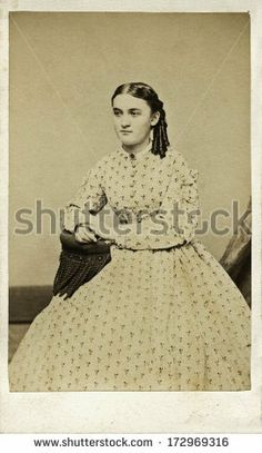CIRCA 1864 - A vintage Cartes de visite photo of young girl sitting in chair with ringlets in hair. She is dressed in hoop skirt dress. Photo from the Victorian era. A digital copy of this photo can be purchased at the above web link.