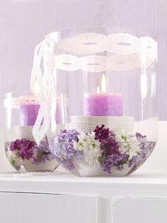Glaswindlicht mit Wasser, Flieder und Kerze