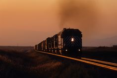 https://flic.kr/p/QWo158 | Louisville sunset | At sunset, Montana Rail Link F45 No. 391 leads ML (Missoula to Laurel manifest) up the grade of Winston Hill east of Helena at Louisville, Montana, on September 2, 2003. Smoke from western wildfires enhances the golden colors of a low setting sun in Big Sky Country.