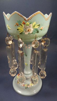 A Victorian glass Table lustre with 8 hanging sections and floral enamel decoration to the blue glass body
