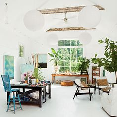 An all-white interior pulls together the open floor plan of this artist's studio and lets the paintings stand out.