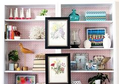 built-in - fabric back with small geometric pattern.  balance of books, accessories and pics.  framed art was added to book case surround for even more depth and style.
