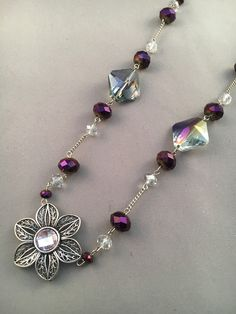 This necklace has purple beads with large smoky acrylic beads with a metal flower with a pink center pendant.