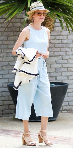 Diane Kruger partied it up at a Memorial Day fete in a summer 3x1 light denim crop top and matching gaucho pants that she styled with a straw fedora and nude strappy stacked heels.