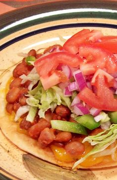 Flavorful beans and crispy vegetables sit atop a flour tortilla made crispy by sauteeing in olive oil.