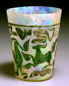 Early Islamic Glass Cup with Cameo Decoration  Glass, 9th-10th century C.E., probably from Iran H. 13.8 cm.   Colorless translucent glass is covered with green semi-translucent glass. The glass was then blown and molded to form, and the decorative pattern was then shaved away form the surface layer.