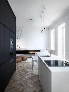 Make your floors the star of the show by using a knotty wood and alternating in shade. The matte black cabinets, otherwise white walls, and neutral, modern decor don't hurt, either.