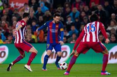 Lionel Messi (C) of FC Barcelona conducts the ball between Saul Niguez (L) and Stefan Savic (R) of Atletico de Madrid during the Copa del Rey semi-final second leg match between FC Barcelona and Atletico de Madrid at Camp Nou on February 7, 2017 in Barcelona, Catalonia.