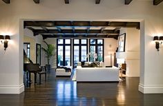 spanish style homes | Foyer in a Spanish revival home with painted black exposed beams and a ...