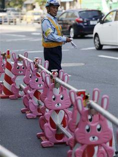A worker stands beside a traffic barrier near a construction site in Tokyo. : Questo è il Giappone che mi ricordo!!! :-)