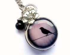 Eine Uhrkette in silber mit einem Vogelmotiv in blau und Schwarz. Angebracht sind ein Blumenanhänger und und eine schwarze Perle.  Ich habe sie e...