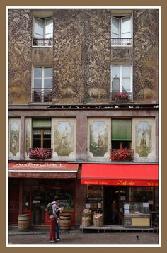 Paris~~Pretty painted house - Paris, Ile-de-France. Is that ironwork or paintings of little pigs on the third floor?  SPECTACULAR!!!!!!!!
