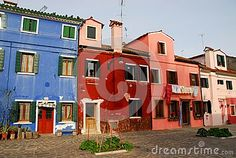 Photo made in the island of Burano in Venice in Italy. In the image are four shooting two colored facades with very intense colors of some houses, narrow to each other, overlooking a courtyard paved with stone eleemnti on which there are two square flower beds framed. Over the colors of the houses you see the pale blue color of the sky.