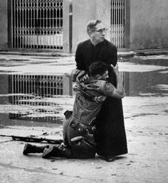 Father Luis Manuel Padilla holds a wounded government rifleman shot down in the streets of Puerto Cabello, Venezuela, during a bloody revolt against President Betancourt in June Photograph by Héctor Rondón Lovera.